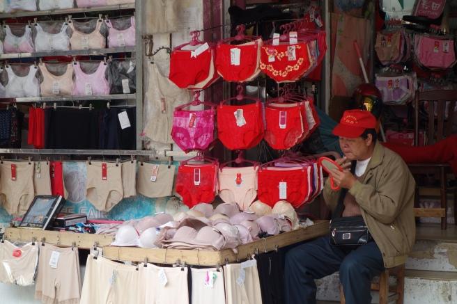 男人卖女人内衣。他的帽子和镜子也是红色。在得胜沙路拍的照片。I snapped this photo while shopping in Hai Sheng Sha Road in Haikou (Hainan Island).
