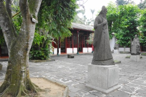 The stone statues of Zhao Ding (赵鼎),  Li Guang (李光) and Hu Quan (胡铨) in the background.